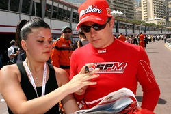 Kimi Raikkonen, Scuderia Ferrari, signs an autograph for a girl
