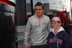 A young fan has his picture taken with Fernando Alonso, McLaren Mercedes