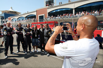 Roberto Carlos, Fenerbahce football player, takes a picture of the Red Bull Racing mechanics