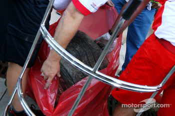 Bridgestone take away tyres from the crash damaged car of Kimi Raikkonen, Scuderia Ferrari