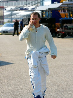 Jacques Villeneuve walks through the garage area