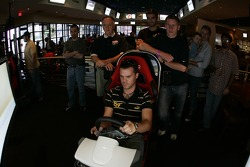 Petit Preview Party at Atlantic Station: Dirk Muller tries the racing sim at the Fox Sports Grill party, while Peter Dumbreck and Lucas Luhr look on