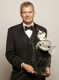 Jeff Burton poses with the trophy given to the eighth place driver in the NASCAR NEXTEL Cup Series standings