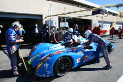 Pescarolo Sport team members at work while Emmanuel Collard sits in the car