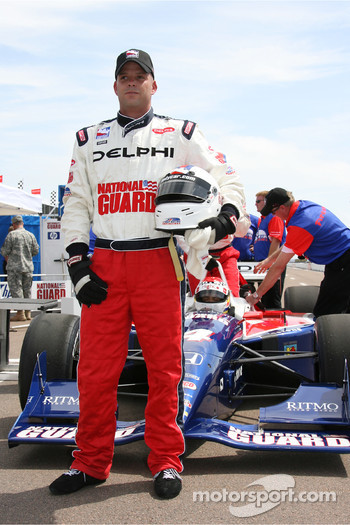 A National Guard man poses before taking a ride in the IndyCar two seater