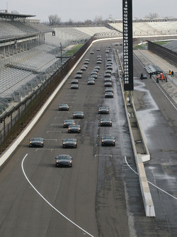 A fleet of Chevrolet Corvettes drives down the main straightaway at the Indianapolis Motor Speedway