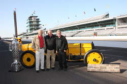 Rick Mears, A.J. Foyt and Al Unser Sr. pose with the Borg Warner trophy and the Marmon Wasp