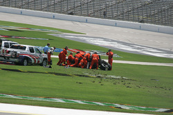 Safety workers try to upright Dan Wheldon's upside down car
