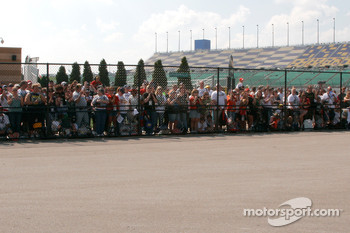 No one in stands but they are all waiting by the garage for the drivers to come in