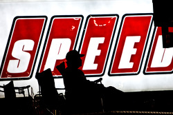 A fan sits atop a truck to watch the race