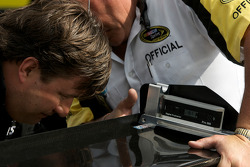 A NASCAR official inspects the rear wing of the Penske Racing Dodge of David Stremme
