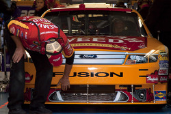 A crew member for Jamie McMurray cleans the front of his car