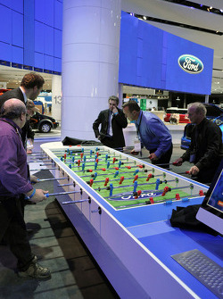 Members of the Ford staff and the media play an impromptu game of foosball at the Ford display on the floor of NAIAS 2010.