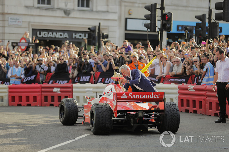 Jenson Button, McLaren, da un paseo de pasajero a Naomi Campbell en 2 plazas y Damon Hill ofrece el trofeo British Grand Prix como una broma