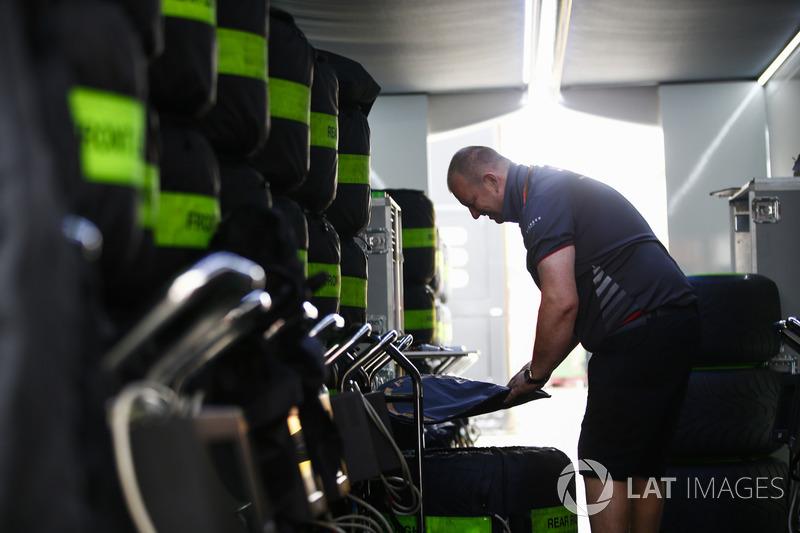 Un miembro del equipo de Haas en el trabajo, en un corredor de neumáticos apilados con mantas