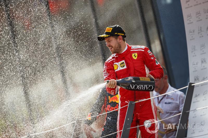 Sebastian Vettel, Ferrari, 3° classificato, spruzza lo Champagne sul podio
