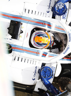 Robert Kubica, Williams FW41, is attended to by mechanics in the pit lane