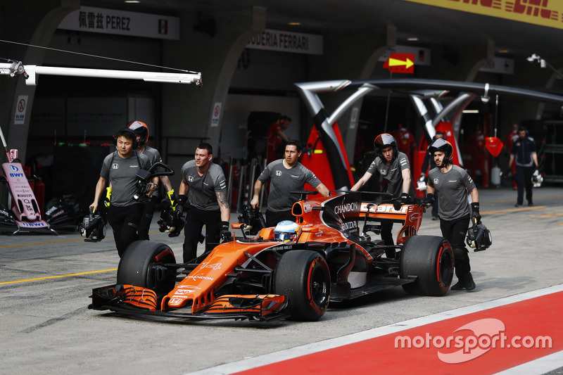 The McLaren team return Fernando Alonso, McLaren MCL32, to the garage