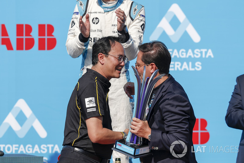 Team member collects the constructors trophy on the podium