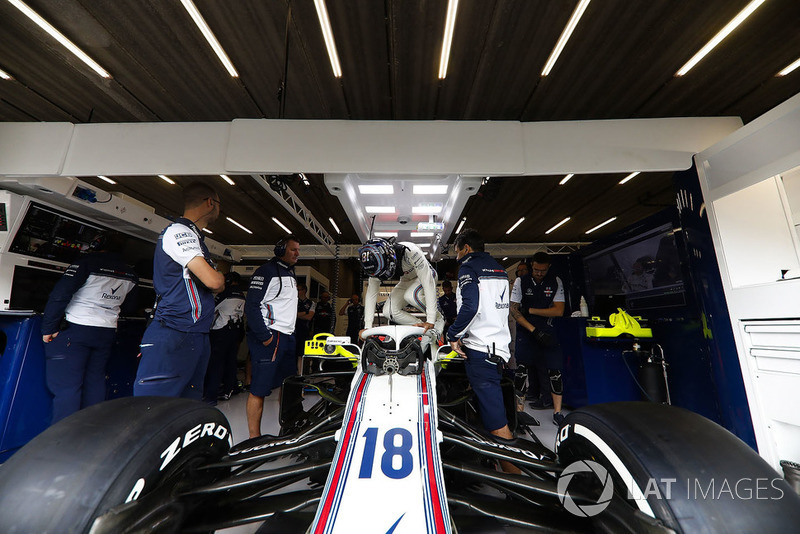 Lance Stroll, Williams FW41, climbs in to his car