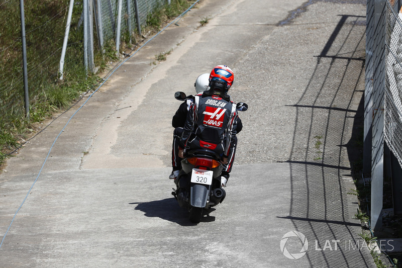 Romain Grosjean, Haas F1 Team VF-18, receives a lift back to the pits on a moped