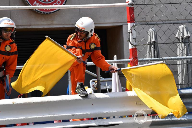 Un comisario agita las banderas amarillas después del accidente de Max Verstappen, Red Bull Racing RB14