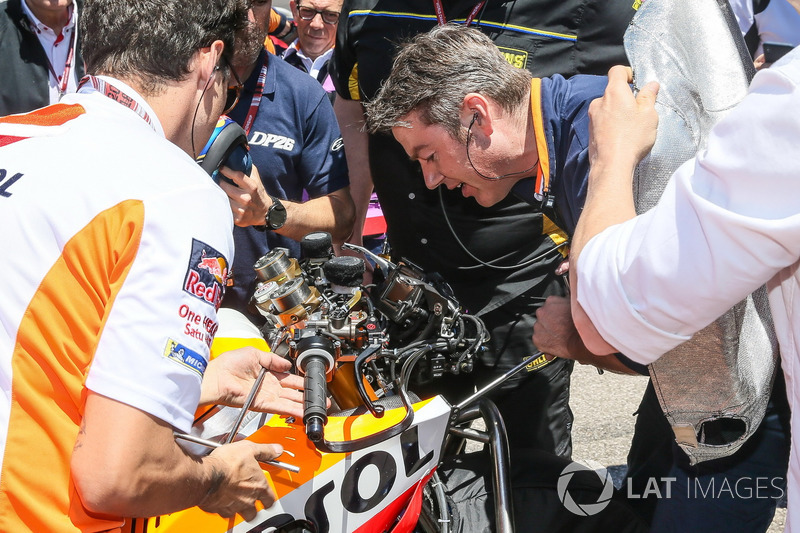 Mechanics make changes to Dani Pedrosa, Repsol Honda Team bike on grid