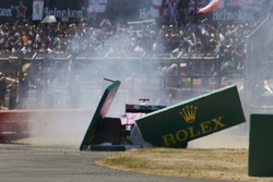Sergio Perez, Force India VJM11, spins out and crashes through a trackside sign at the start
