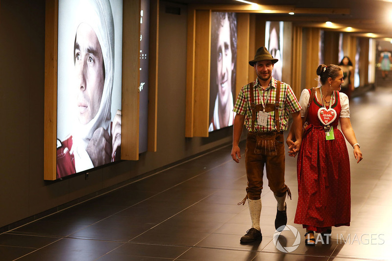 Болельщики в национальных костюмах проходят по галерее чемпионов