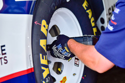 A crew member tightening up a lug nut