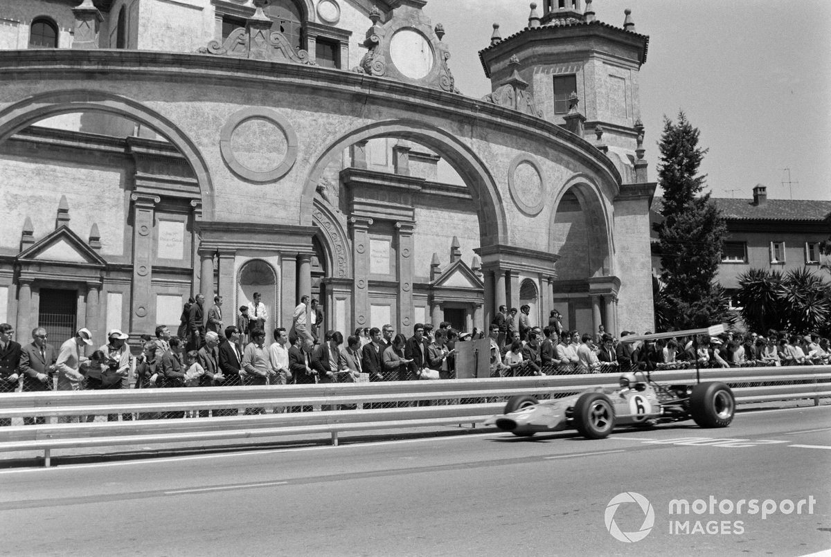 Bruce McLaren passes the Palacio de la Agricultura, now a theatre, in the 1969 Spanish Grand Prix