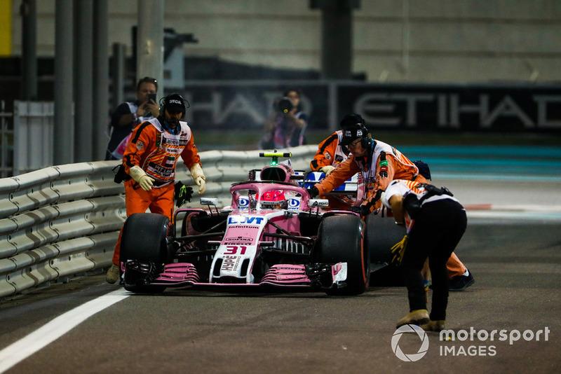 Oficiales mueven el auto de Esteban Ocon, Racing Point Force India VJM11, mientras se retira de la carrera por problemas técnicos
