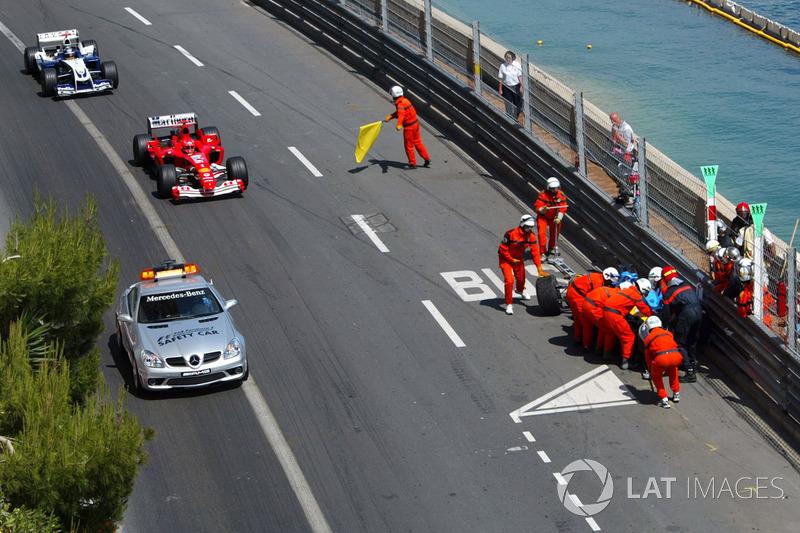 Renault R24 Фернандо Алонсо прибирають маршали, а Михаель Шумахер, Ferrari F2004, слідує за машиною безпеки попереду Хуана Пабло Монтойї, Williams BMW FW26