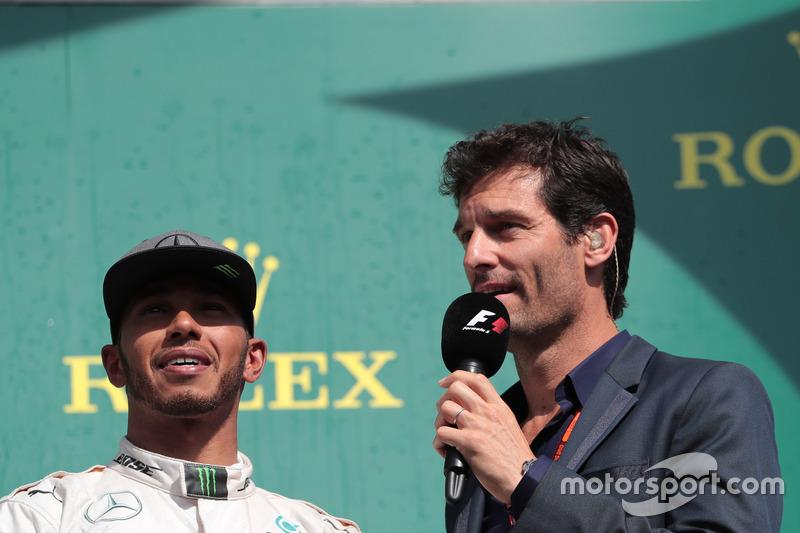 (Da sx a dx): Lewis Hamilton, Mercedes AMG F1 sul podio con Mark Webber, pilota Porsche Team WEC / Presentatore Channel 4