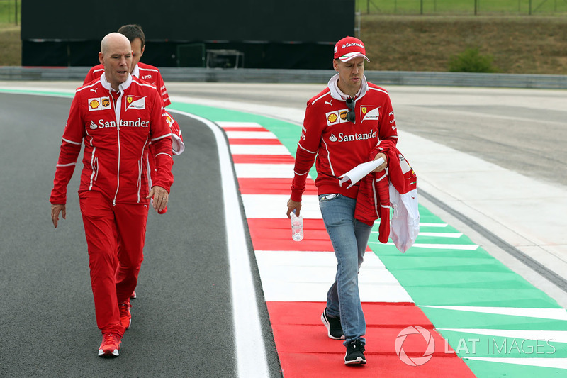 Sebastian Vettel, Ferrari y Jock Clear, Ferrari jefe de ingenieros caminan en la pista