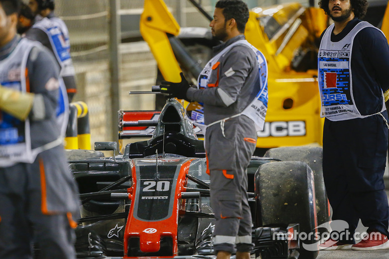 Marshals applaud the drivers on the podium beside the car of Kevin Magnussen, Haas F1 Team VF-17 Ferrari