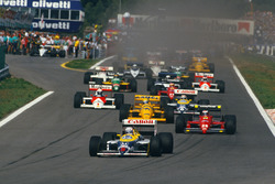 Nigel Mansell, Williams FW11B Honda, leads Gerhard Berger, Ferrari F187, Ayrton Senna, Lotus 99T Honda, Nelson Piquet, Williams FW11B Honda, and Alain Prost, McLaren MP4/3 TAG Porsche, at the start