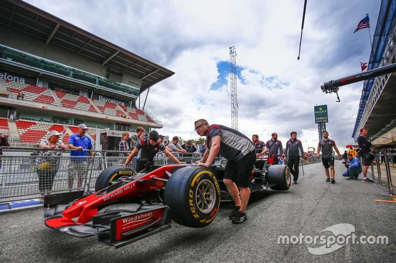 Механики Haas F1 толкают VF-17 Кевина Магнуссена по пит-лейну