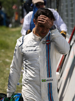 Race retiree Felipe Massa, Williams walks back after after crashing out of the race