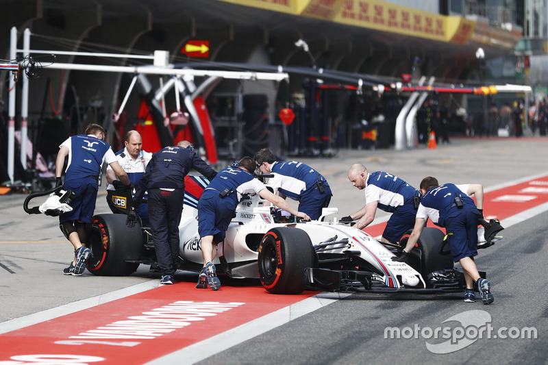 The Williams team return Felipe Massa, Williams FW40, to the garage