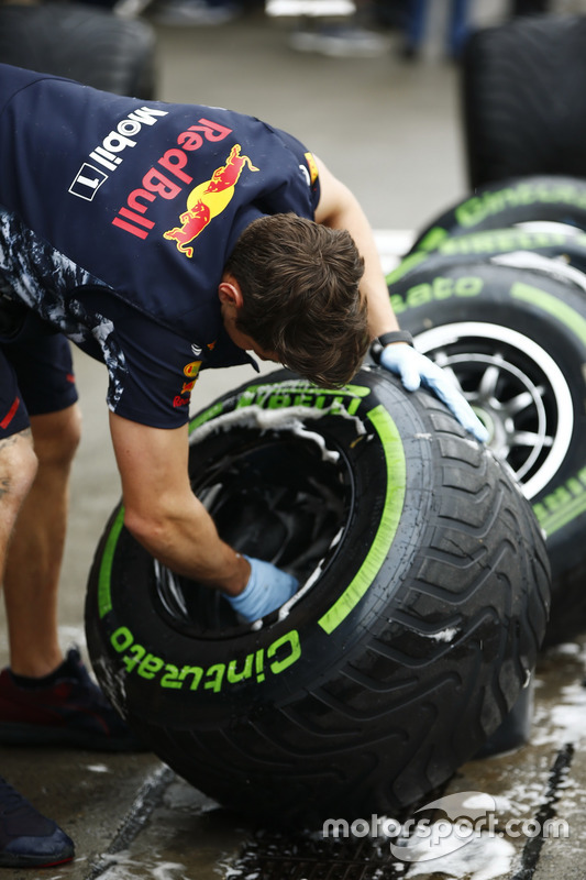 A Red Bull mechanic washes some Intermediate tyres
