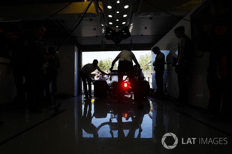 McLaren engineers return a car to the garage