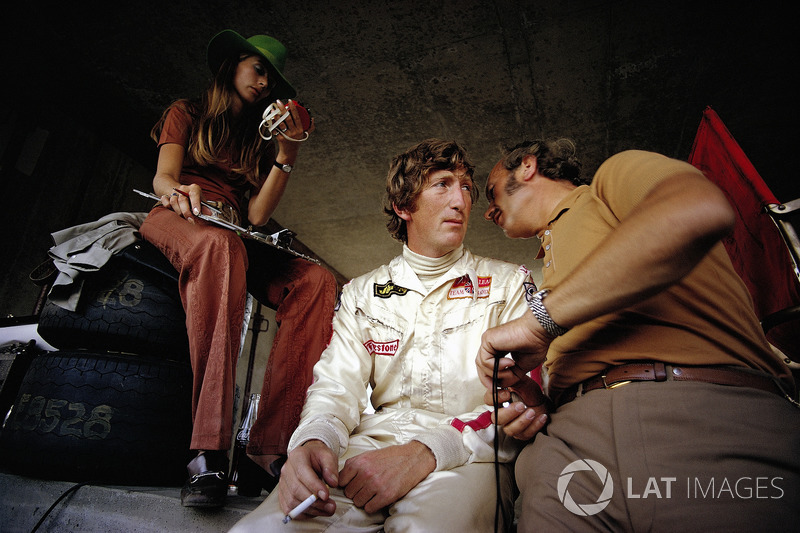 Jochen Rindt in pits with his time-keeping wife Nina and Lotus team boss Colin Chapman