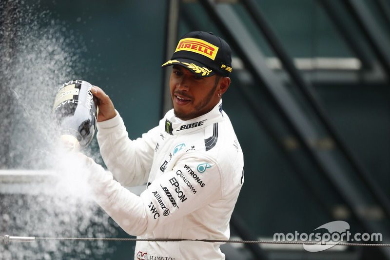Lewis Hamilton, Mercedes AMG, celebrates victory by spraying chamagne on the podium