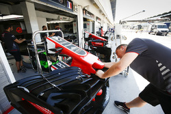 Haas F1 Team members prepare a front wing in the pits