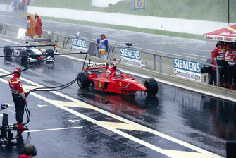 Michael Schumacher, Ferrari F300, with missing front wheel and wing, and David Coulthard, McLaren MP4-13 Mercedes, with missing rear wing, in the pitlane