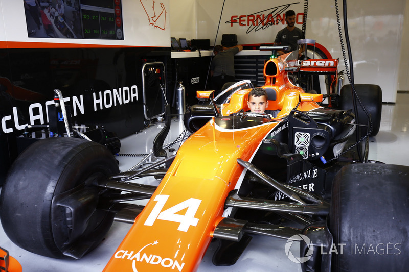A young fan sits in the cockpit of the Fernando Alonso McLaren MCL32