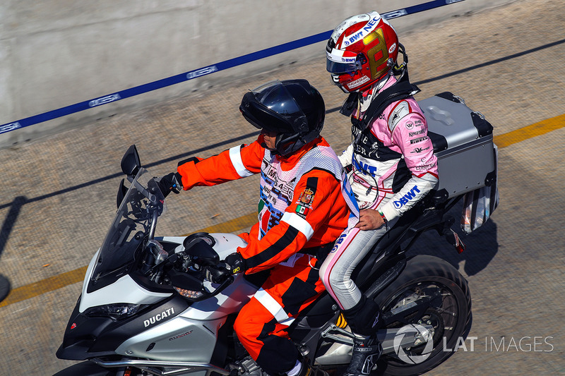 Alfonso Celis Jr., Sahara Force India regresa al pit en una moto con un oficial de pista tras estrellarse en FP1