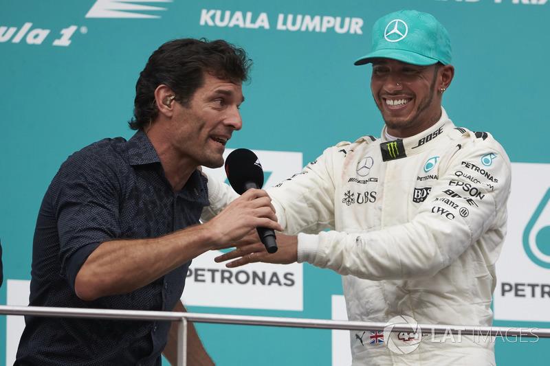 Mark Webber, TV Pundit, Channel 4 F1, interviews second place Lewis Hamilton, Mercedes AMG F1, on the podium