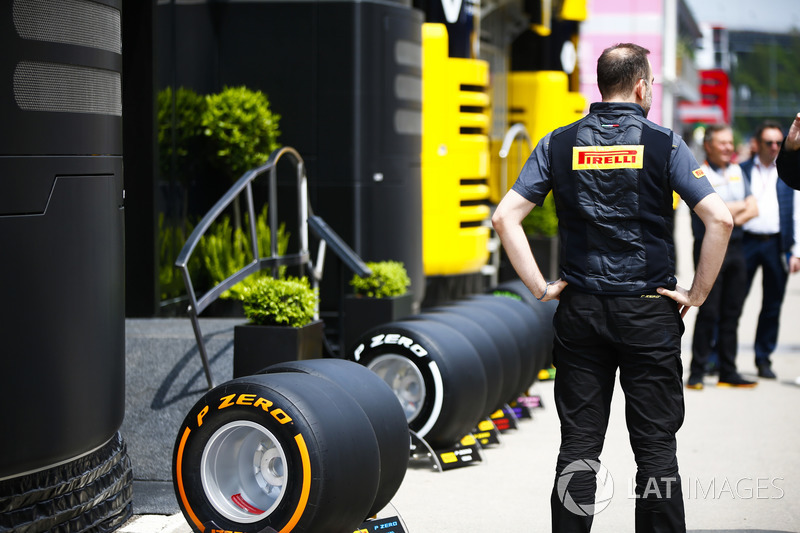A Pirelli employee stands next to a line of tyres outside of the company's motorhome